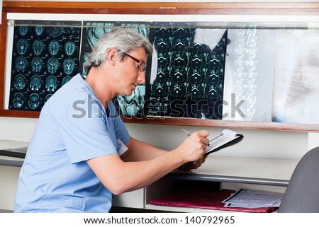Mature male doctor at desk writing on clipboard with MRI x-rays on wall - stock photo