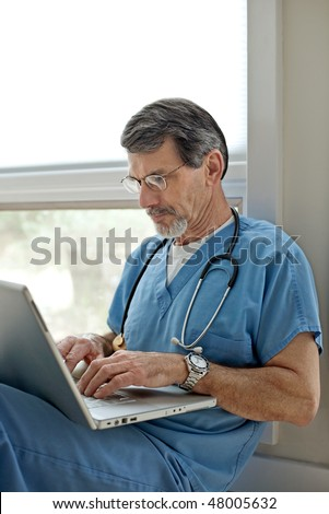Mature male doctor seated on floor, working on laptop computer - stock photo