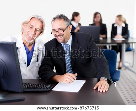 Mature male doctor showing patient prescription on his computer - Colleagues in the background - stock photo