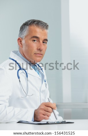 Mature male doctor sitting at desk in doctor's room - stock photo