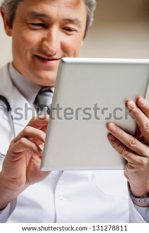 Mature male doctor smiling while using digital tablet - stock photo