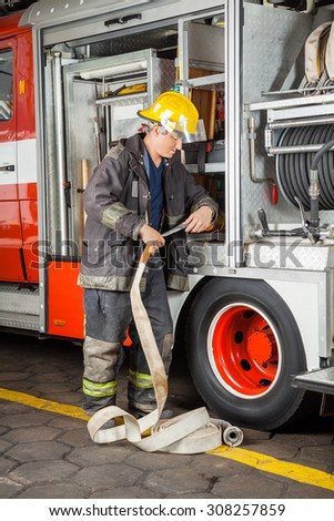 Mature male firefighter adjusting hose in truck at fire station