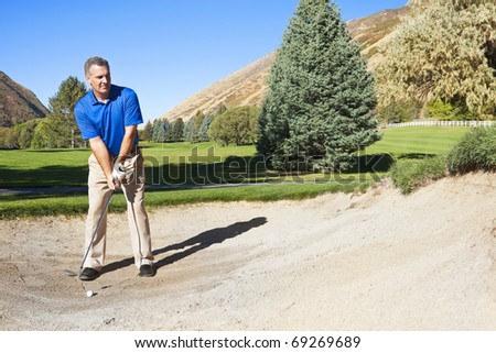 Mature male golfer about to hit out of a sand bunker - stock photo