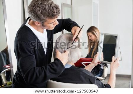 Mature male hairdresser cutting client's hair with woman in the background at salon - stock photo