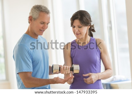 Mature male instructor assisting woman in lifting dumbbell at gym - stock photo