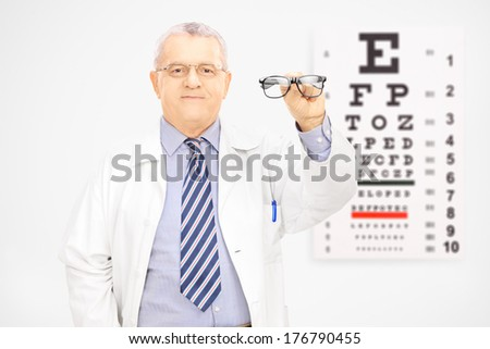Mature male optician holding a pair of glasses in front of an eye chart isolated on white background