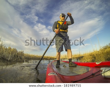 mature male paddler enjoying workout on an inflatable stand up paddleboard (SUP), calm lake in one of nature areas in Fort Collins, Colorado,  distorted wide angle view - stock photo