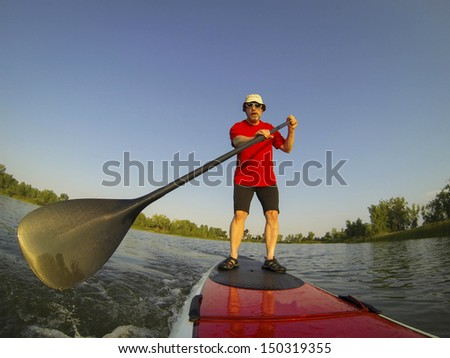 mature male paddler enjoying workout on stand up paddleboard (SUP), calm lake in Colorado, summer, distorted wide angle view - stock photo