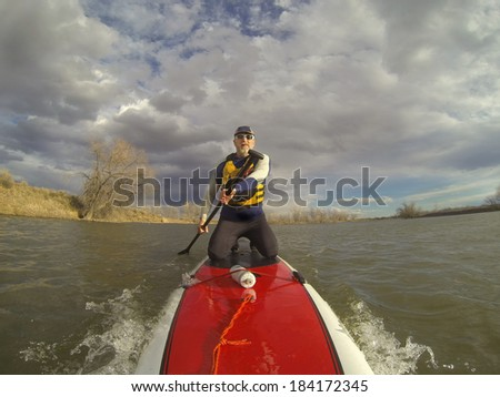mature male paddler in wetsuit and life jacket enjoying workout on a stand up paddleboard (SUP), windy lake in one of nature areas in Fort Collins, Colorado,  distorted wide angle view - stock photo