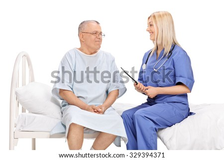 Mature male patient and a young female doctor having a conversation seated on a hospital bed isolated on white background
