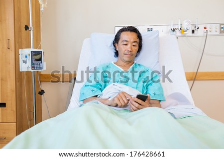 Mature male patient text messaging through cell phone on bed in hospital