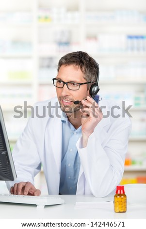 Mature male pharmacist wearing headset while using computer at pharmacy counter - stock photo