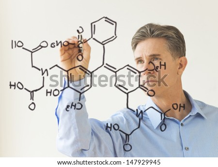Mature male scientist drawing molecular structure on transparent board against white wall - stock photo