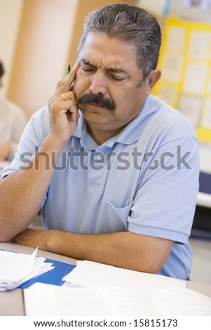 Mature male student frowning in class - stock photo