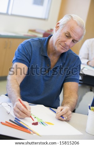 Mature male student in art class - stock photo