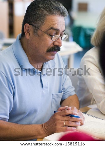 Mature male student studying in library - stock photo