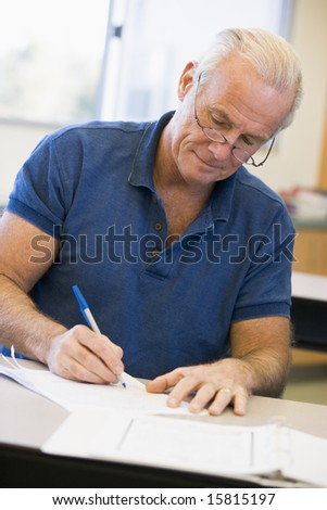 Mature male student writing in class - stock photo