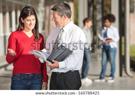 Mature male teacher and student discussing over book on college campus