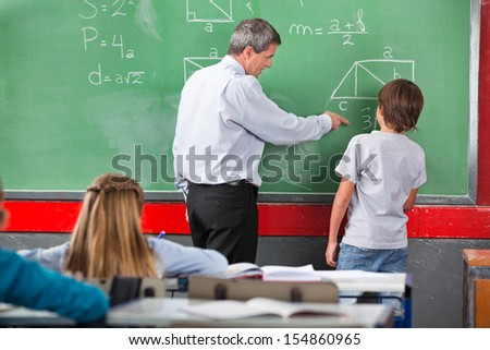 Mature male teacher assisting little schoolboy while solving mathematics on board in classroom - stock photo