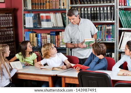 Mature male teacher communicating with students sitting at table in library
