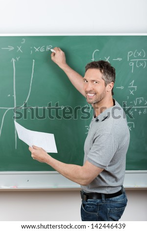 Mature male teacher holding paper while writing on chalkboard in classroom - stock photo