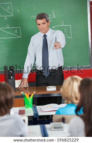 Mature male teacher pointing at students while teaching in classroom - stock photo