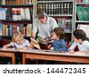 Mature male teacher showing book to schoolboy with students studying at table in library - stock photo