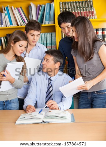 Mature male teacher with books explaining students in college library