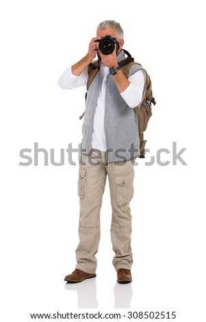 mature male tourist taking pictures with digital camera - stock photo