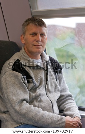mature male traveler in a gray cardigan sits in a car of a train and looks at you - stock photo