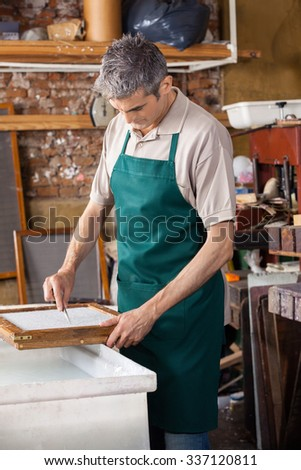 Mature male worker cleaning paper with tweezers in factory - stock photo