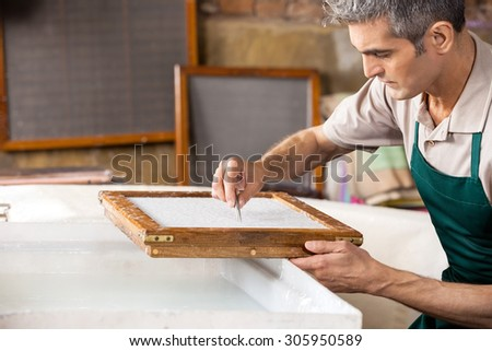 Mature male worker cleaning paper with tweezers over vat in factory - stock photo