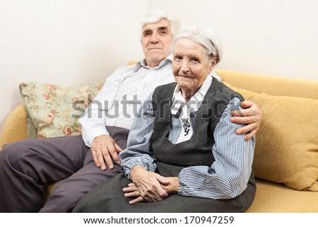 Mature man and senior woman sitting on sofa  - stock photo