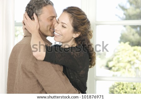 Mature man and woman hugging and whispering in each other's ear. - stock photo