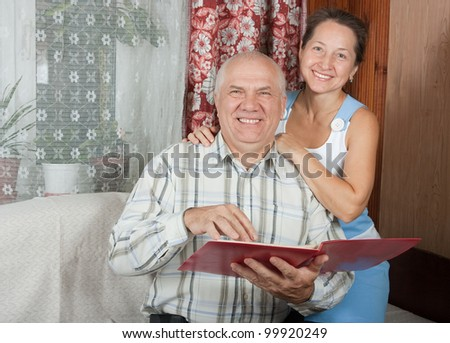 Mature man and woman on sofa at home - stock photo