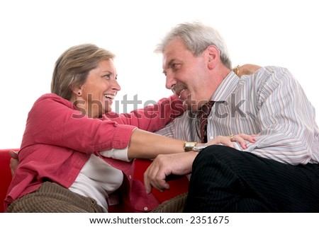 Mature man and woman sits on the couch and smiles to each other - stock photo