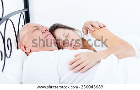 Mature man and woman sleeping   in   bedroom
