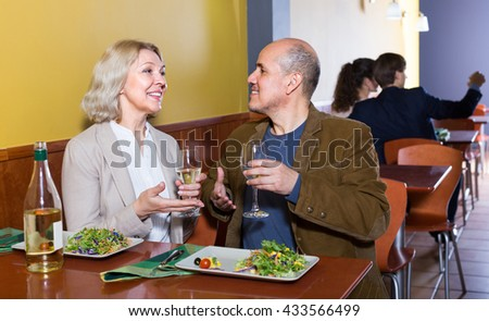 Mature man and woman spending time together in restaurant - stock photo