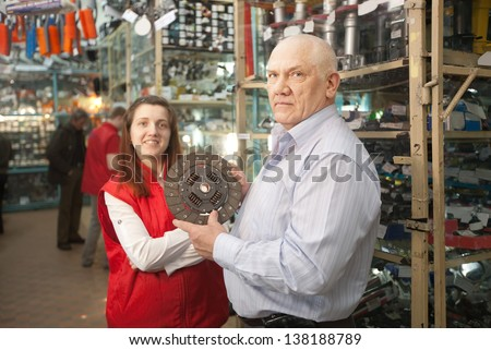 mature man and woman with  clutch  in  auto parts store - stock photo