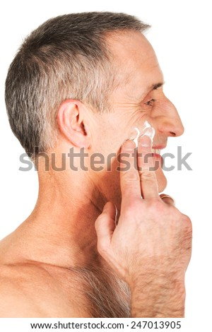 Mature man applying cream on his face. - stock photo
