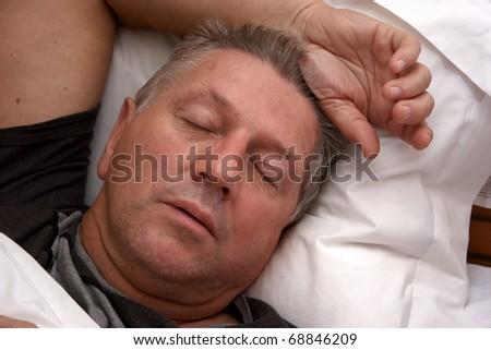 Mature man asleep in bed - stock photo
