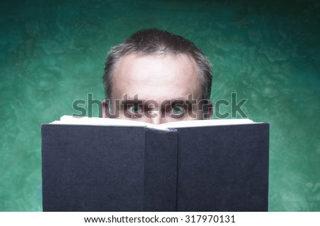 Mature man being focused and hooked by book, reading open book, surprised young man, amazing eyes looking blank cover, green background - stock photo