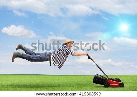 Mature man being pulled by a powerful lawnmower outdoors on a beautiful sunny day - stock photo