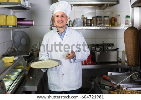 Mature man chef wearing uniform cooking kebab on kitchen in fast-food cafe