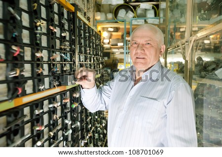 mature man chooses fasteners in  auto parts store - stock photo