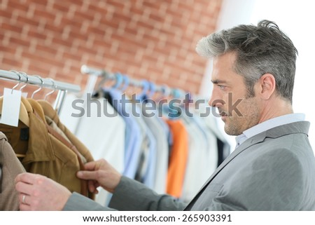 Mature man choosing clothes in shop - stock photo