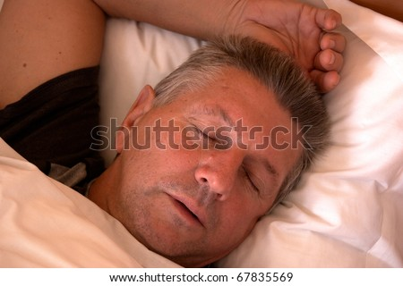 Mature man clothed and asleep in bed - stock photo