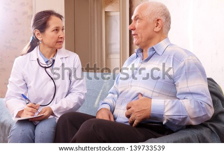 Mature man complaining  to doctor about tummy-ache at medical hospital - stock photo