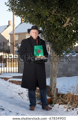 Mature man delivering christmas presents in the snow