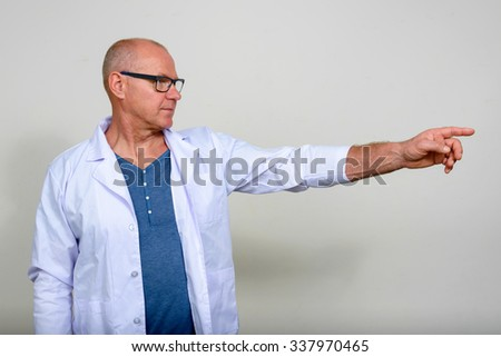 Mature man doctor pointing finger
